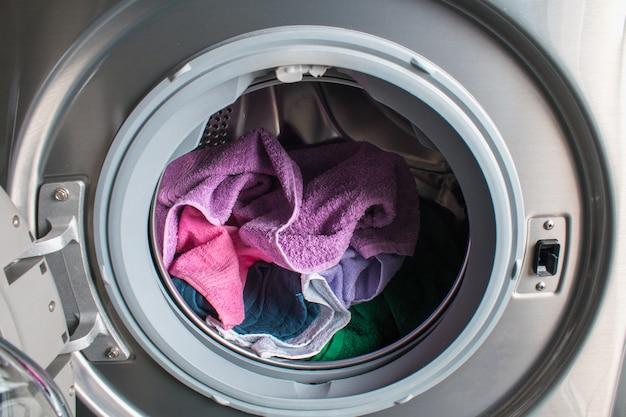 Mężczyzna bierze koloru ubrania od pralki. bęben pralki pełnej brudnej bielizny w łazience.