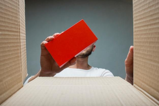 Mężczyzna bierze małe pudełko z zamówieniem z otwartego pudełka. widok od wewnątrz. concept otrzymał paczkę, zamówienie, mogazin internetowy, dostawę towaru, zakupy online.