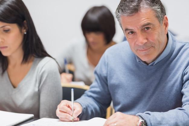 Mężczyzna bierze notatki w wykładzie
