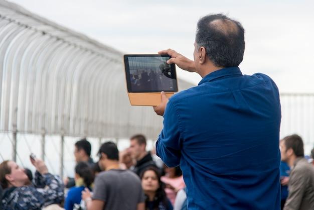 Mężczyzna bierze obrazki z ipad przy empire state building obserwatorium, manhattan, miasto nowy jork, nowy
