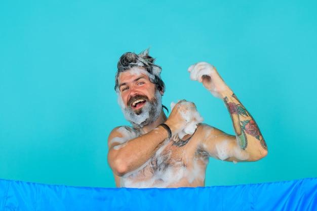 Mężczyzna bierze prysznic mężczyzna w piance mycie głowy brodaty mężczyzna mycie włosów pielęgnacja włosów spa kąpiel czas ciało