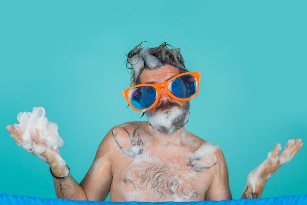 Mężczyzna bierze prysznic mężczyzna z pianką na głowie mężczyzna pielęgnacja włosów mycie ciała brodaty mężczyzna bierze prysznic włosy