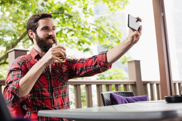 Mężczyzna bierze selfie podczas gdy mieć napój