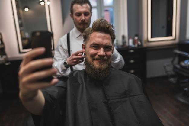 Mężczyzna bierze selfie z fryzjerem męskim