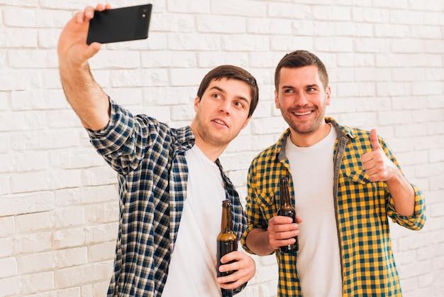 Mężczyzna bierze selfie z jego przyjacielem na smartphone pozyci przeciw białemu ściana z cegieł