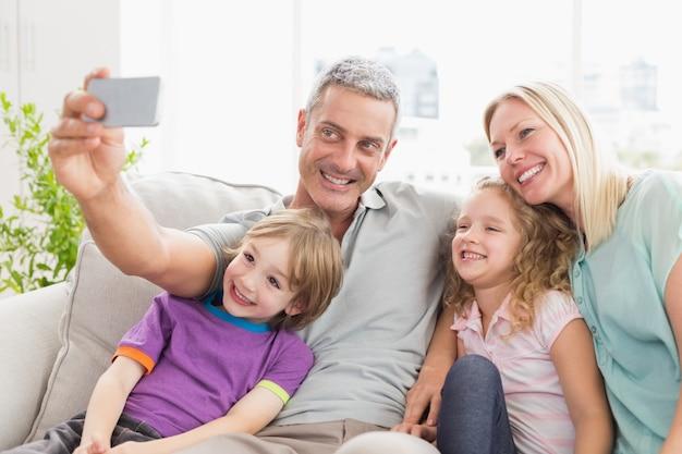 Mężczyzna bierze selfie z rodziną na kanapie