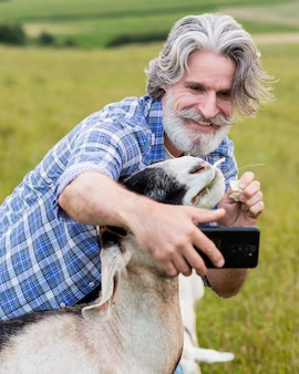 Mężczyzna bierze slefie z kozą