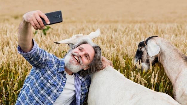 Mężczyzna bierze slefie z kozami