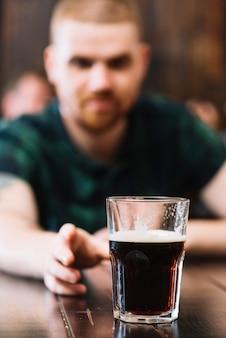 Mężczyzna bierze szkło rum nad biurkiem