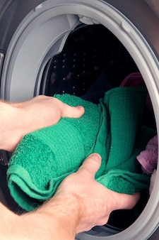 Mężczyzna bierze ubrania z pralki