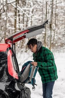 Mężczyzna biorąc plecak z samochodu