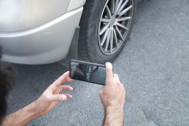 Mężczyzna biorąc zdjęcie samochodu na swoim telefonie.