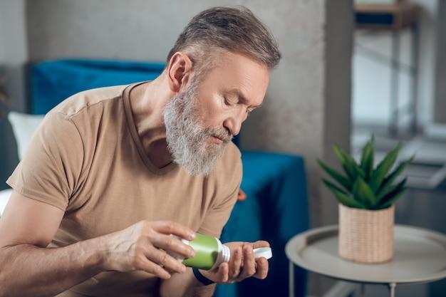 Mężczyzna biorący pigułkę z zielonego słoika
