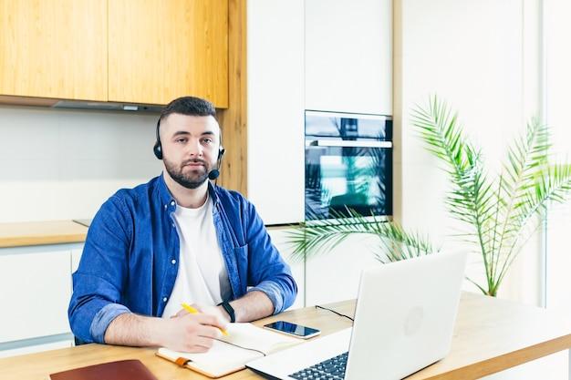 Mężczyzna biznesmen patrzy na przód używa zestawu słuchawkowego i używa połączenia wideo do konsultacji online biznesmen pracuje w domu
