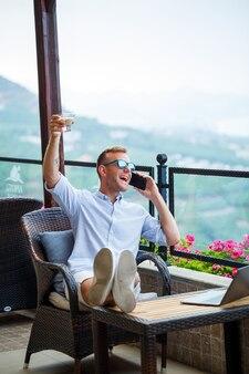 Mężczyzna biznesmen pracuje na laptopie na wakacjach z pięknym widokiem na panoramę. skuteczny menedżer pije kawę i rozmawia przez telefon z kawą podczas podróży