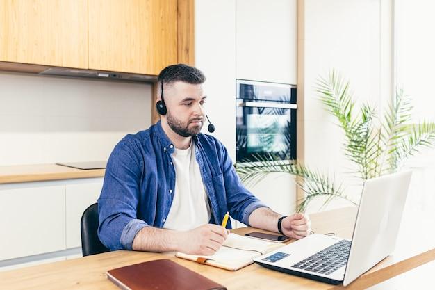Mężczyzna biznesmen pracuje w domu i za pomocą zestawu słuchawkowego i laptopa. pracownik patrzy na ekran komputera i przeprowadza konsultację online