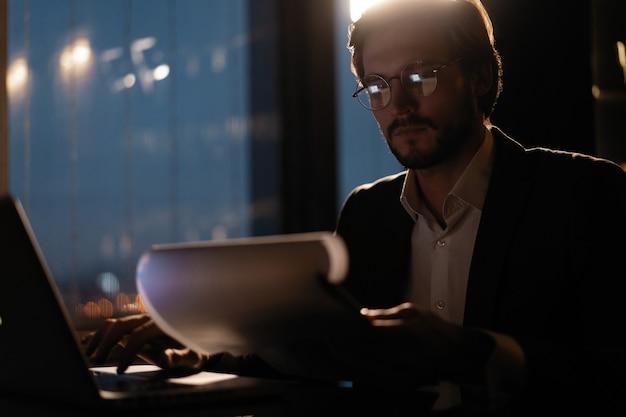 Mężczyzna biznesmen pracuje z raportów biznesowych i wykresów finansowych. papierkowa robota późno w nocy.