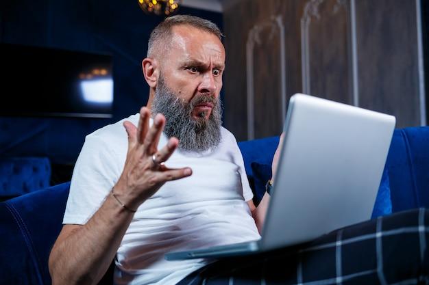 Mężczyzna biznesmen siedzi przy filiżance kawy i robi nowy projekt z grymasami na twarzy.