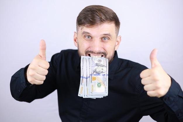 Mężczyzna biznesmen trzyma pieniądze w zębach i daje kciuki do góry