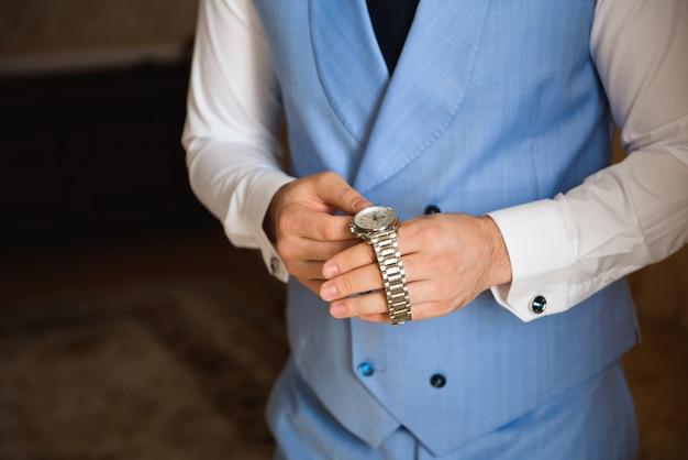 Mężczyzna biznesmen ubiera i dostosowuje zegarek, przygotowując się do spotkania. zegar