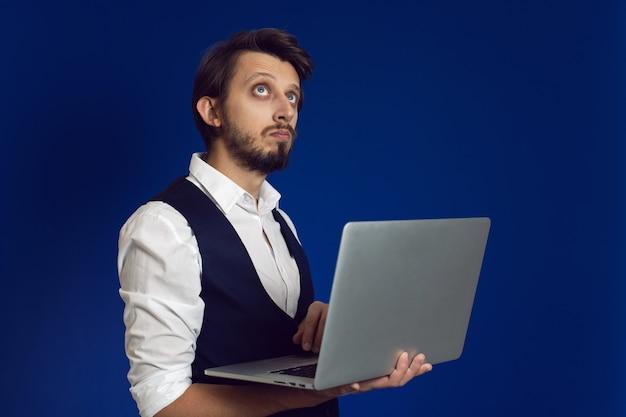 Mężczyzna biznesmen z brodą w białej koszuli i kamizelce trzyma laptopa na niebieskiej ścianie