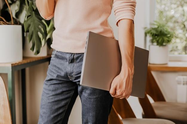 Mężczyzna biznesmen z laptopem w obszarze roboczym w kawiarni eco z roślinami