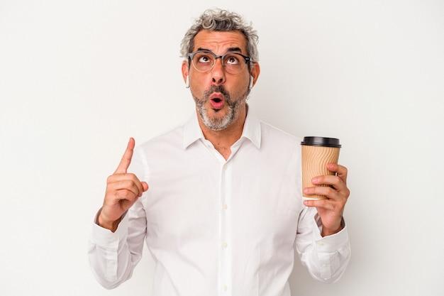 Mężczyzna biznesu w średnim wieku trzyma kawę na wynos na białym tle, wskazując do góry nogami z otwartymi ustami.