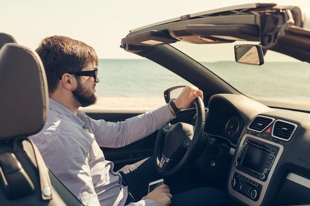 Mężczyzna blisko kabrioletu samochodu outdoors