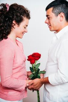 Mężczyzna blisko młodej szczęśliwej kobiety z świeżymi kwiatami