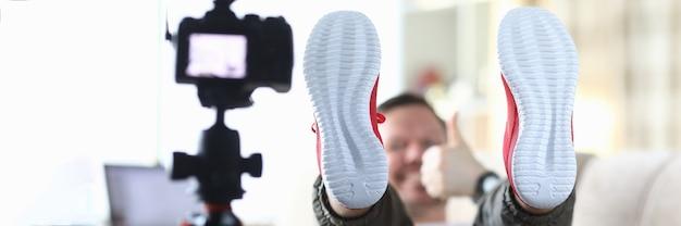 Mężczyzna bloger demonstruje podeszwę swoich tenisówek przed kamerą
