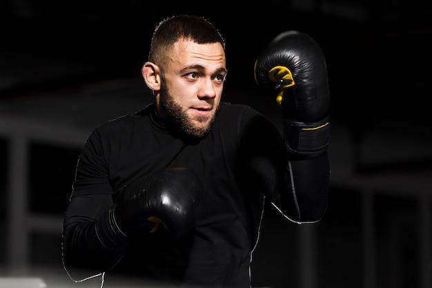 Mężczyzna bokser pozuje w ochronnych rękawiczkach