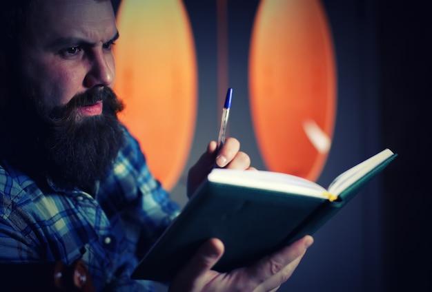 Mężczyzna brodaty wypełnia pamiętnik