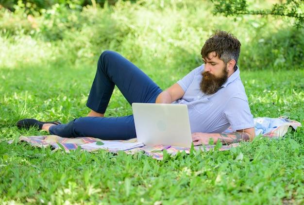 Mężczyzna brodaty z laptopem relaksujący łąka tło natura. pisarz szukający inspiracji w przyrodzie. inspiracja do blogowania. bloger inspiruje się naturą. szukać inspiracji.