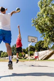 Mężczyzna broniący koszykówki rzuconej przez drugą drużynę w obręczy