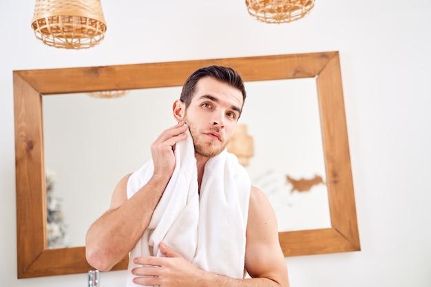 Mężczyzna brunet wyciera ręcznik, stojąc przy lustrze w wannie