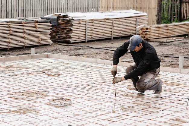 Mężczyzna budowlaniec przygotowuje pręt zbrojeniowy do posadowienia budowy domu i wylewania betonu