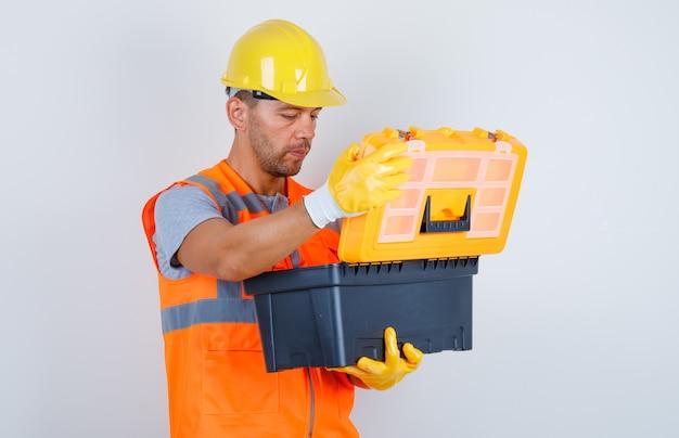 Mężczyzna budowniczy otwierający plastikową skrzynkę na narzędzia w mundurze, hełmie, rękawiczkach, widok z przodu.