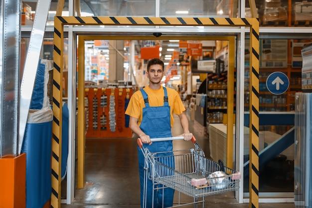 Mężczyzna budowniczy przewozi materiały budowlane w wózku, sklepie z narzędziami. klient patrzy na towary w sklepie dla majsterkowiczów