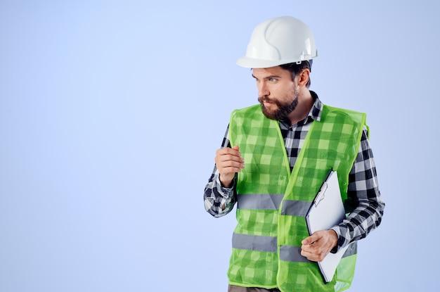 Mężczyzna budowniczy w branży studia projektowego w zielonej kamizelce budowlanej