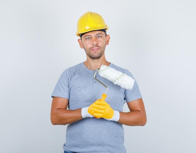 Mężczyzna budowniczy w koszulce, kasku, rękawiczkach trzymających wałek do malowania, widok z przodu.