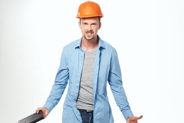Mężczyzna budowniczy w niebieskiej koszuli emocje profesjonalne jasne tło