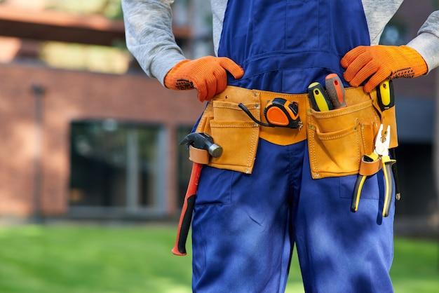 Mężczyzna budowniczy w niebieskim kombinezonie noszącym pasek narzędziowy. zamknij obszar talii