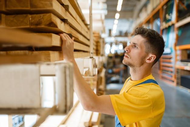 Mężczyzna budowniczy wybiera materiały naprawcze w sklepie z narzędziami. klient patrzy na towary w sklepie dla majsterkowiczów