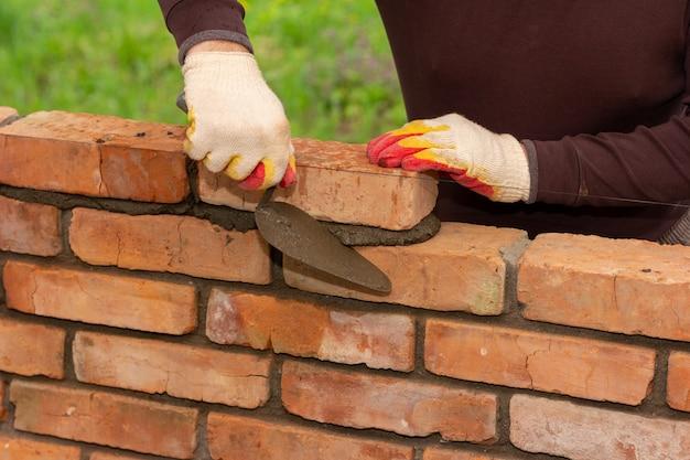 Mężczyzna buduje mur z cegieł, kładzie cegłę na zaprawie cementowo-piaskowej