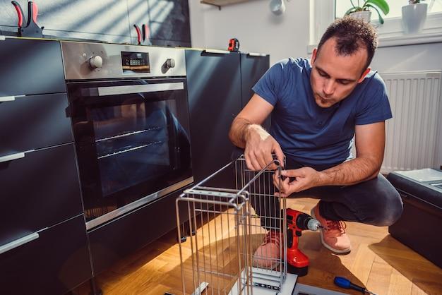 Mężczyzna buduje szafki kuchenne
