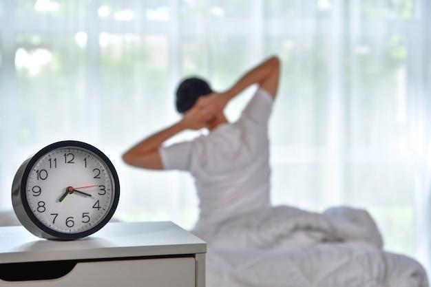 Mężczyzna budzący się rano, siedzący na łóżku i rozciągający się, skupiający się na budziku