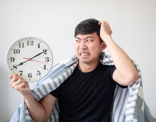 Mężczyzna budzi się późno, czuje zszokowaną głowę z kołdrą na ciele i patrzy na zegar w dłoni