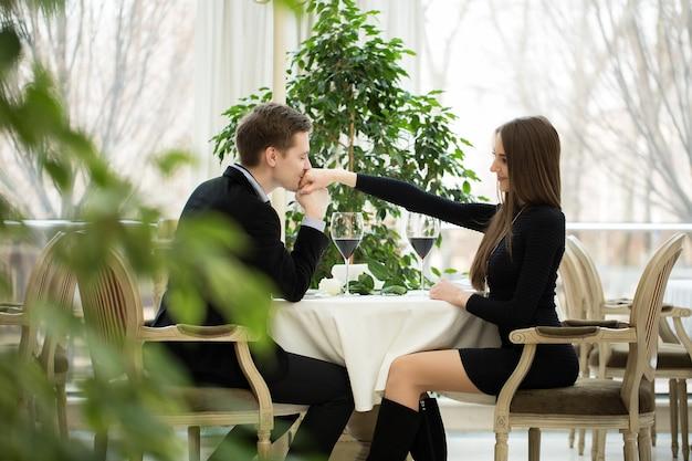 Mężczyzna całujący kobietę w rękę podczas romantycznej kolacji, która patrzy na niego z uwielbionym wyrazem twarzy i uroczym uśmiechem