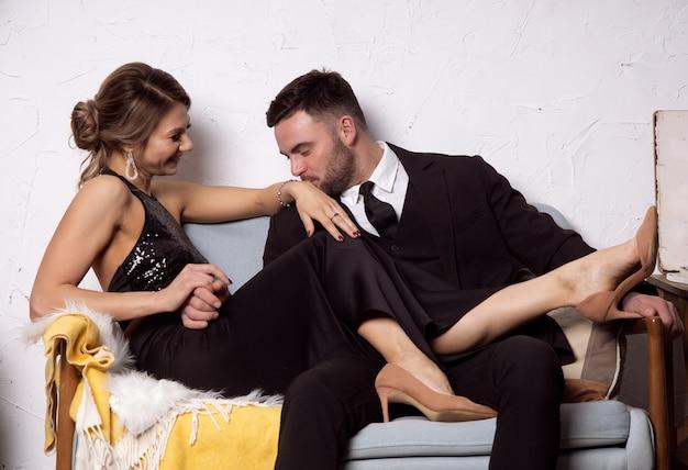 Mężczyzna całuje dłonie roześmianej dziewczyny, szczęśliwa para siedzi na kanapie