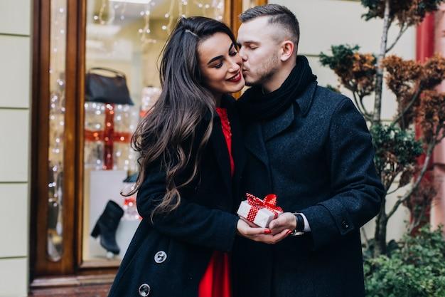 Mężczyzna całuje dziewczynę na prezent świąteczny